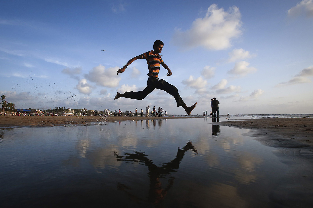 A man jumps over a water stream on a beach along the Arabian Sea in Mumbai