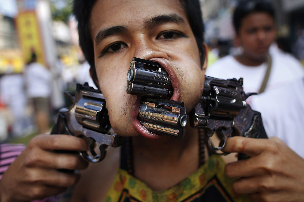 A devotee, with two guns pierced through his cheeks, takes part in a street procession during the annual vegetarian festival in Phuket